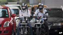 Pengendara motor menggunakan masker saat mengendarai kendaraannya melintasi jalanan kota New Delhi, India (Foto: dok). Ibukota India memulai tahun baru dengan eksperimen yang dirancang untuk mengurangi polusi udara yang memecahkan rekor di kota itu.