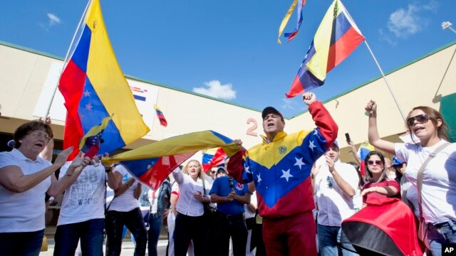 Dozens of demonstrators chant and wave Venezuelan flags in Doral, Florida, Feb. 18, 2014.