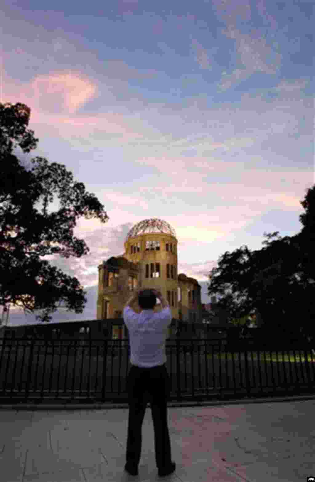 A man takes pictures of the Atomic Bomb Dome at sunset in Hiroshima, western Japan, Friday, Aug. 5, 2011 on the eve of the 66th anniversary of the world's first atomic bombing on the city. (AP Photo/Koji Sasahara)
