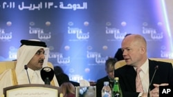Britain's Foreign Secretary William Hague (R) talks with Qatar's Crown Prince Sheikh Tamim bin Hamad al-Thani before the start of the first contact group meeting on Libya in Doha, Qatar, April 13, 2011