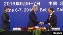 Menlu AS John Kerry berjabat tangan dengan wakil Perdana Menteri China, Wang Yang dalam dialog AS-China di Beijing (7/6).