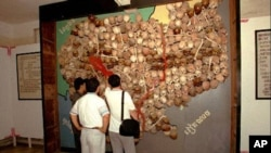 Visitors to Toul Sleng, officially known as S-21 prison look at a wall of sculls and bones made into a map of Cambodia.