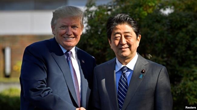 美国总统川普与日本首相安倍晋三在霞关乡村俱乐部前握手。(2017年11月5日)