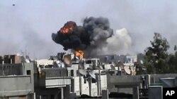 敘利亞政府軍4月18日砲擊中部城市霍姆斯﹐有建築受襲擊後升起濃煙。