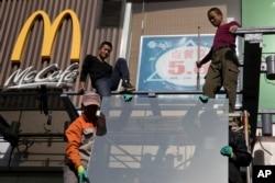 ພວກພະນັກງານກຳລັງຕິດຕັ້ງແກ້ວກະຈົກ ໃກ້ໆກັບຮ້ານອາການ McDonald ໃນປັກກິ່ງ, 7 ພະຈິກ, 2017. ປະທານາທິບໍດີສະຫະລັດ ທ່ານດໍໂນລ ທຣຳ ກຳລັງຢ້ຽມຢາມ ປັກກິ່ງ, ທ່າມກາງການຕຳໜິຕິຕຽນເລື່ອງການຄ້າ ທີ່ຈຳກັດ ການເຂົ້າເຖິງຕະຫຼາດ, ນະໂຍບາຍດ້ານເທັກໂນໂລຈີ ແລະອື່ນໆ ທີ່ສູງຂຶ້ນນັ້ນ..