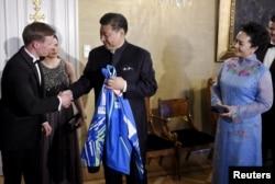 中国主席习近平和夫人在芬兰赫尔辛基参加国宴前,接受芬兰国家滑雪队赠送的运动衣(2017年4月5日)。习近平夫妇将从芬兰来到美国。
