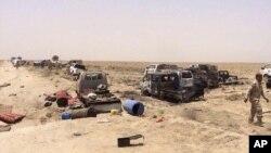 نیروهای امنیتی عراقی در ال بررسی خودروهای منهدم شده پیکارجویان داعش که در حال فرار از فلوجه بودند - ۹ تیر ۱۳۹۵
