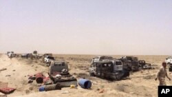 Petugas keamanan Irak memeriksa kendaraan militan ISIS yang melarikan diri di luar Fallujah, Irak (29/6).