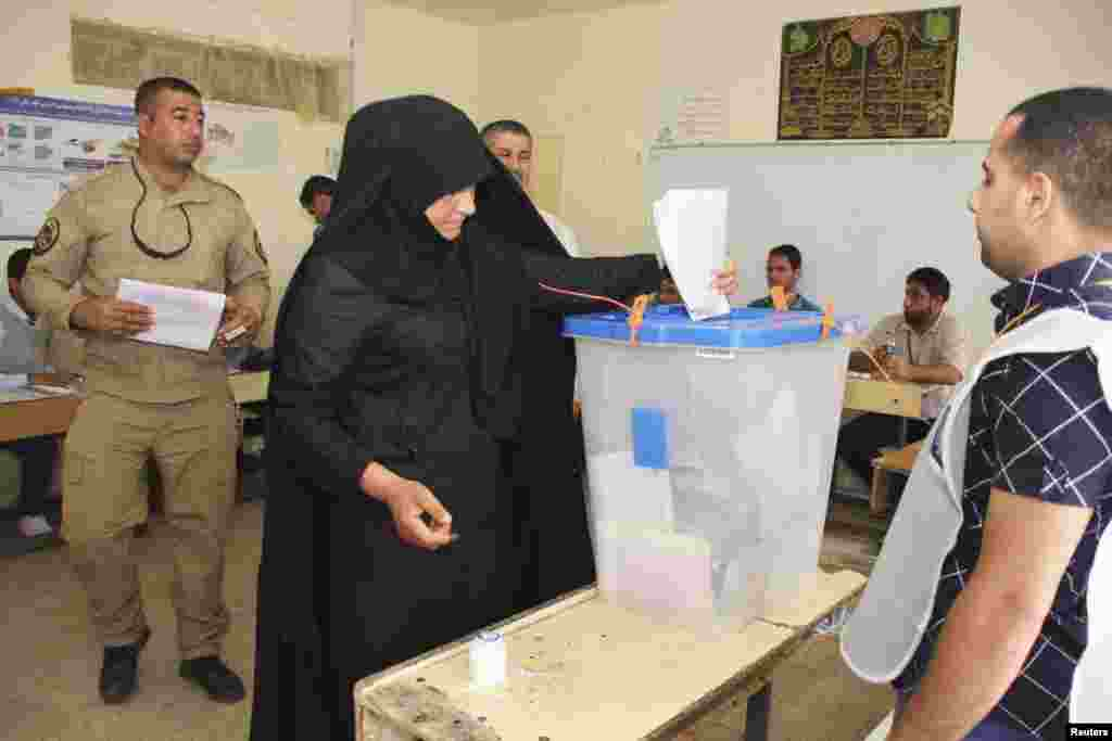 A police officer casts her ballot inside a polling station during early voting for the parliamentary election, in the Sadr City district of Baghdad, April 28, 2014. Iraq will be holding its national elections on April 30. REUTERS/Wissm al-Okili (IRAQ - Ta