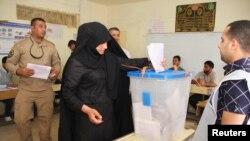 Un officier de police place son bulletin de vote dans une urne lors du vote anticipé dans le cadre des élections législatives, dans le quartier de Sadr City à Bagdad, le 28 Avril 2014.REUTERS / Wissm al-Okili