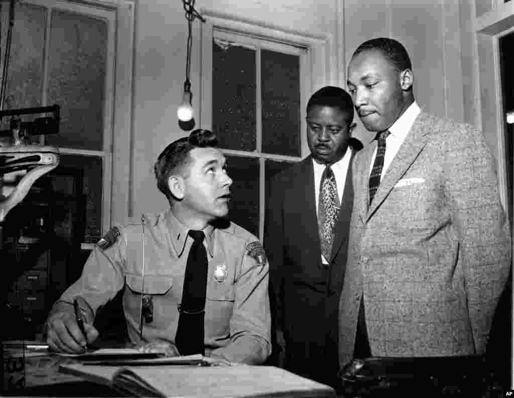 Martin Luther King, Jr., accompanied by Rev. Ralph D. Abernathy is booked by city police Lt. D.H. Lackey in Montgomery, Alabama, Feb. 23, 1956.