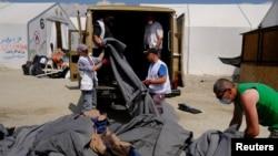 2016年5月26日,警察在希腊和马其顿边界附近拆除临时难民营地,工人们在整理毯子。(路透社)