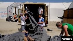 Radnici raščišćavaju kamp u Idomeniju posle evakuacije migranata, 26. maj 2016.