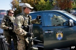 FILE - Fighters from the Azov volunteer battalion arrive on rotation from the front line in Kyiv, Ukraine, Sept. 15, 2014.