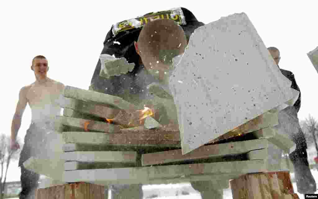 Pripadnik specijalnih snaga bjeloruskog Ministarstva unutranjih poslova razbija cementne ploče u plamenu tokom jedne pokazne vježbe.