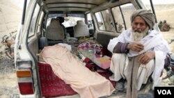 Seorang warga Afghanistan menunggu jenazah korban penembakan tentara AS di Panjwai, Kandahar (11/3).