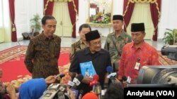 "Usai bertemu Presiden Jokowi, Presiden ketiga RI BJ Habibie memperlihatkan buku biografinya berjudul ""RUDY"" kepada wartawan di Istana Merdeka, Jakarta, 13 Oktober 2015 (Foto: VOA/Andylala)"