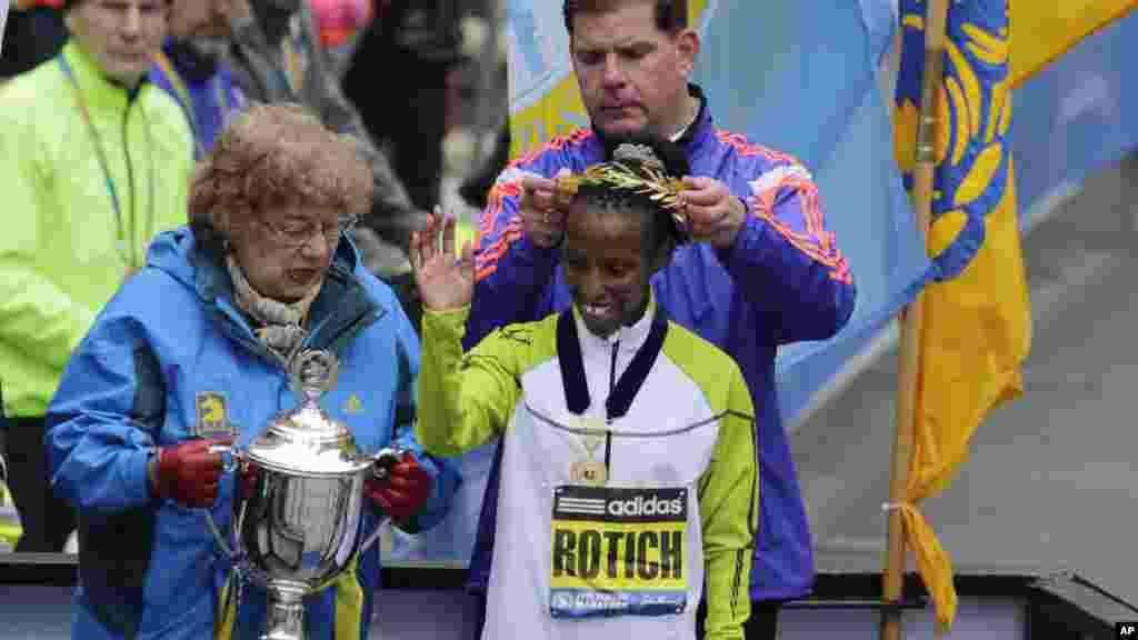 Meya wa Boston Marty Walsh amvaza taji Caroline Rotich, wa Kenya, baada ya kushinda upande wa wanawake mbio za Boston Marathon.