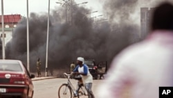De la fumée s'élève alors que les militaires burkinabè, à l'arrière, néttoient les débris laissés par les manifestants sur une rue de Ouagadougou, au Burkina Faso, 18 septembre 2015.