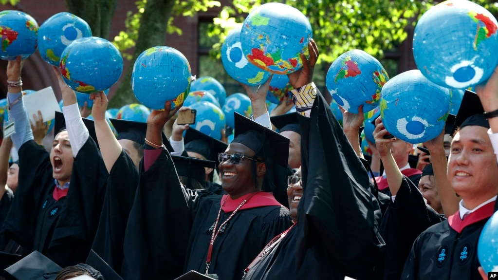 Public policy and government graduate students hold inflatable globes during Harvard University commencement exercises, Thursday, May 24, 2018, in Cambridge, Mass. (AP Photo/Michael Dwyer)