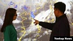 23일 한국 기상청 직원들이 천리안 위성으로 관측된 한반도의 황사를 살펴보고 있다. 푸른색으로 표시된 부분은 황사를 나타내고, 붉은 점은 중국에서 황사가 관측된 지점을 나타낸다.