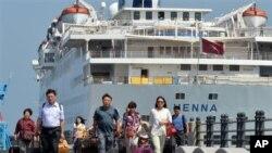 乘客离开停靠在韩国济州岛的中国游轮海娜号
