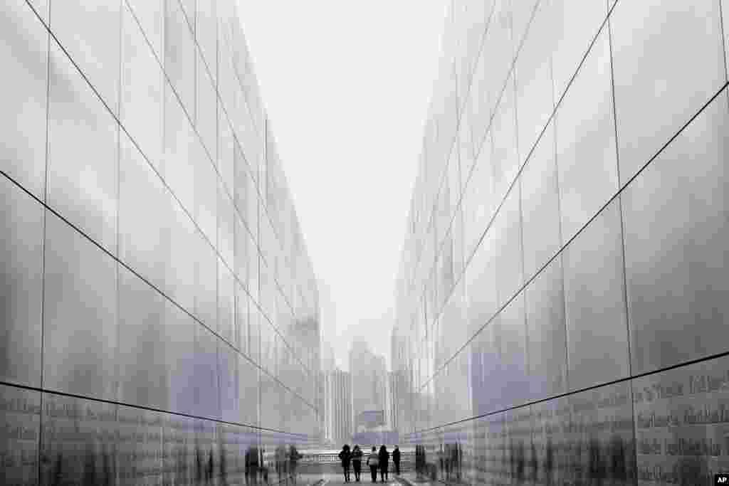 """Wisatawan berjalan melalui """"Empty Sky Memorial"""" di Jersey City, New Jersey dengan latar belakang pemandangan kota New York pada suatu hari yang mendung dan berkabut."""