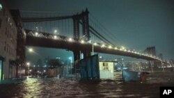 Banjir menggenangi jalanan di bawah Jembatan Manhattan di kota New York akibat badai Sandy. (AP/Bebeto Matthews)