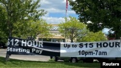 FILE - : A banner inviting people to apply for open jobs is seen outside a McDonald's restaurant in Bloomington, Indiana, May 14, 2021.