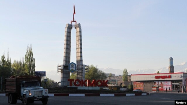 A truck drives past a sign at the entrance to the Kyrgyz city of Tokmok, April 20, 2013.