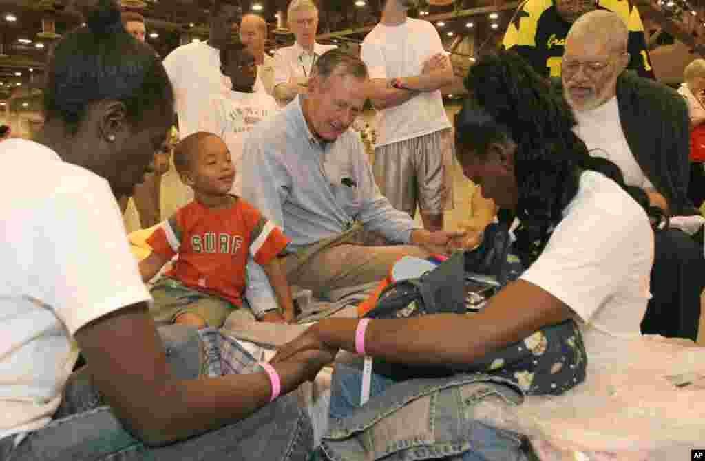 Cựu Tổng thống George H.W. Bush cầu nguyện với nạn nhân bão Katrina Rebecca Solomon, Terrill Hoskins, LaShonda Hoskins và Ernie Ladd tại Trung tâm Reliant giáp với vận động trường Astrodome ở Houston, ngày 5/9/2005.