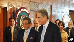Pakistan's Foreign Minister Shah Mehmood Qureshi, right, walks with his Indian counterpart S.M. Krishna, left, as they arrive for talks in Islamabad, 15 July 2010