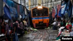 FILE - A Train arrives in Maeklong, in Samut Songkhram province, Thailand.