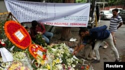 People place flowers at a makeshift memorial near the site, to pay tribute to the victims of the attack on the Holey Artisan Bakery and the O'Kitchen Restaurant, in Dhaka, Bangladesh, July 5, 2016.
