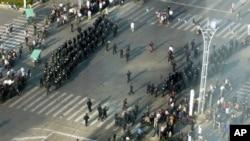 警察2012年10月27日在浙江省宁波市镇海区驱散在街头聚集的人群