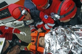 The surviving mother of a baby girl rescued from a collapsed building is taken to an ambulance in Ercis, near the eastern Turkish city of Van, October 25, 2011.