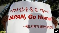 一名示威者手举标语牌因日韩领土争端在日本驻首尔大使馆前抗议