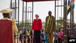 La chancelière allemande Angela Merkel (à gauche) aux côtés du président du Burkina Faso, Roch Marc Christian Kabore lors d'une cérémonie de bienvenue au palais présidentiel de Ouagadougou le 1er mai 2019.