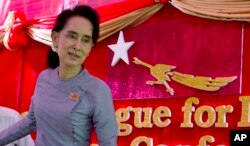 FILE - Myanmar's opposition leader Aung San Suu Kyi leaves a news conference at her home in Yangon, Myanmar.