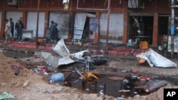 Security forces inspect scene of suicide bombing at a coffee shop, Kirkuk, Iraq, July 13, 2013.
