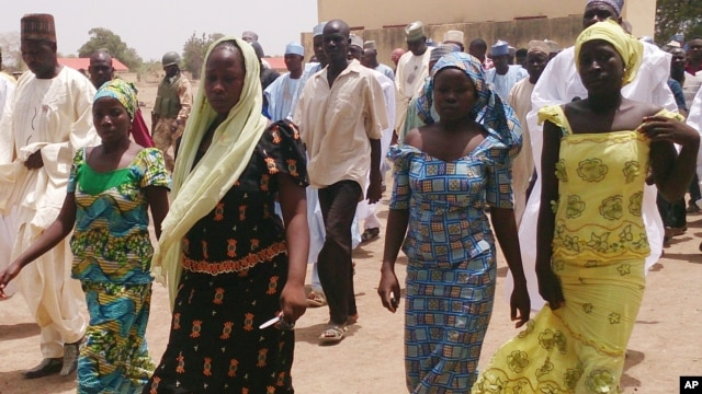Four female students of government secondary school Chibok, who were abducted by gunmen and reunited with their families walk in Chibok, Nigeria, April 21, 2014.