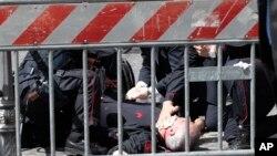 이탈리아 총리실 앞에서 총상을 입은 경찰이 현장에서 응급조치를 받고 있다.