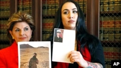 Former Marine Erika Butner, right, stands with attorney Gloria Allred holding photos of Butner in uniform as she and another active-duty female Marine said photographs of them were secretly posted online without their consent, at a news conference in Los Angeles, March 8, 2017.