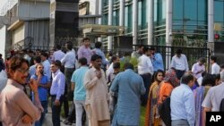 People stand outside their office building after a 6.2 earthquake is felt in Islamabad, Pakistan, Wednesday, May 9, 2018.