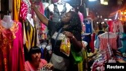 资料照:一名非洲妇女在中国广州的一个服装市场购物。(2014年10月25日)