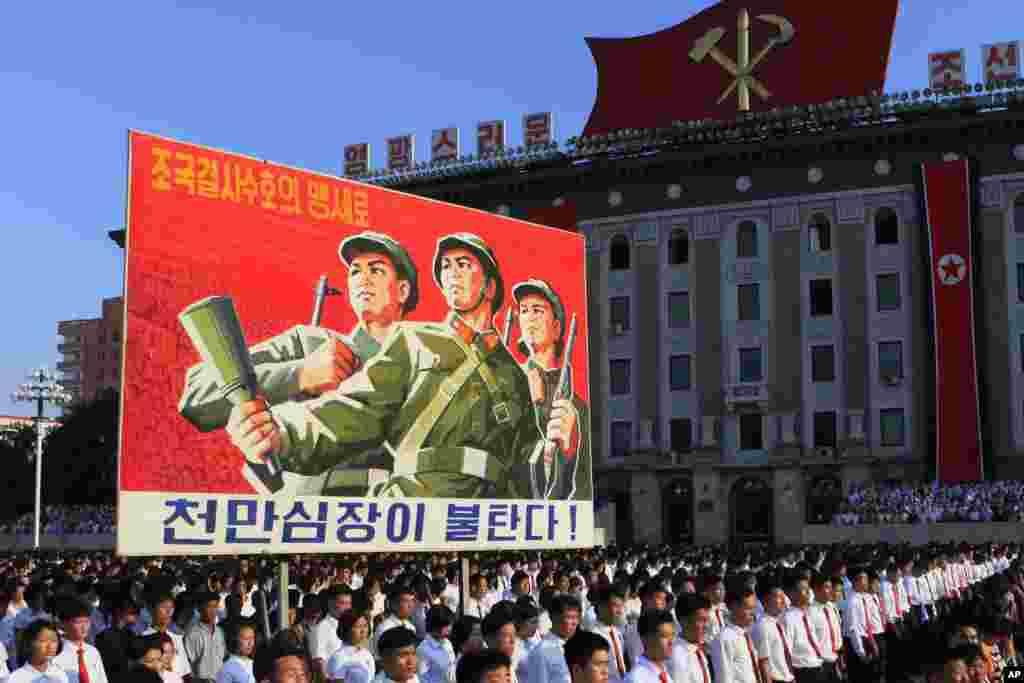 평양시 군중집회에 참가한 청년들이 '조국결사수호의 맹세로 천만심장이 불탄다!'라는 선전문구 주변에 서 있다.