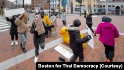 Pro-Thai democracy protesters dance around the monument during the demonstration at King Bhumibol Adulyadej Square in Cambridge, MA Nov 22, 2020.