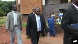 FILE: Elton Mangoma, center, Zimbabwe's Minster of Energy and Power Development outside the magistrates courts, accompanied by two unidentified police detectives in Harare, March, 11, 2011