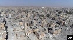 Una imagen de Raqqa tomada de un video de drone muestra decenas de edificios dañados en Raqqa, Siria, dos días después que las Fuerzas Democráticas Sirias dijeran que las operaciones militares para desalojar al Estado Islámico habían terminado. Oct. 19, 2017.