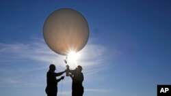 Mike Newchurch, left, professor of atmospheric chemistry at the University of Alabama in Huntsville, and graduate student Paula Tucker prepare a weather balloon before releasing it to perform research during the solar eclipse, Aug. 21, 2017, on the Orchar